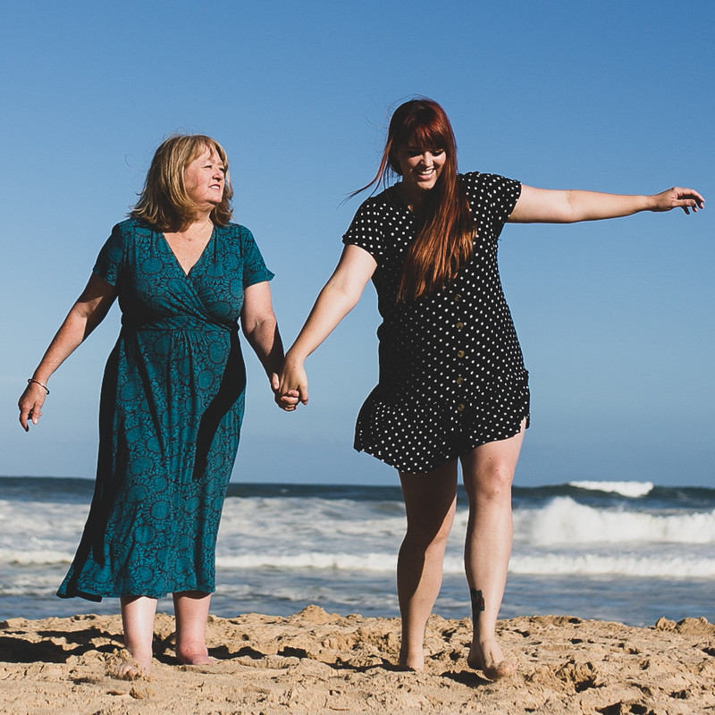 See You Later Mum - A photo of two women holding hands walking along the beach. the woman on the left has blonde hair and is wearing a teal coloured dress. The woman on the right has long auburn hair is wearing a black and white dress.