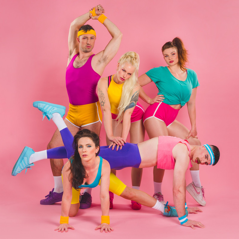 Five performers all wearing very bright and colourful workout gear, in front of a bight pink background. They are flexing muscles, posing and doing push ups.