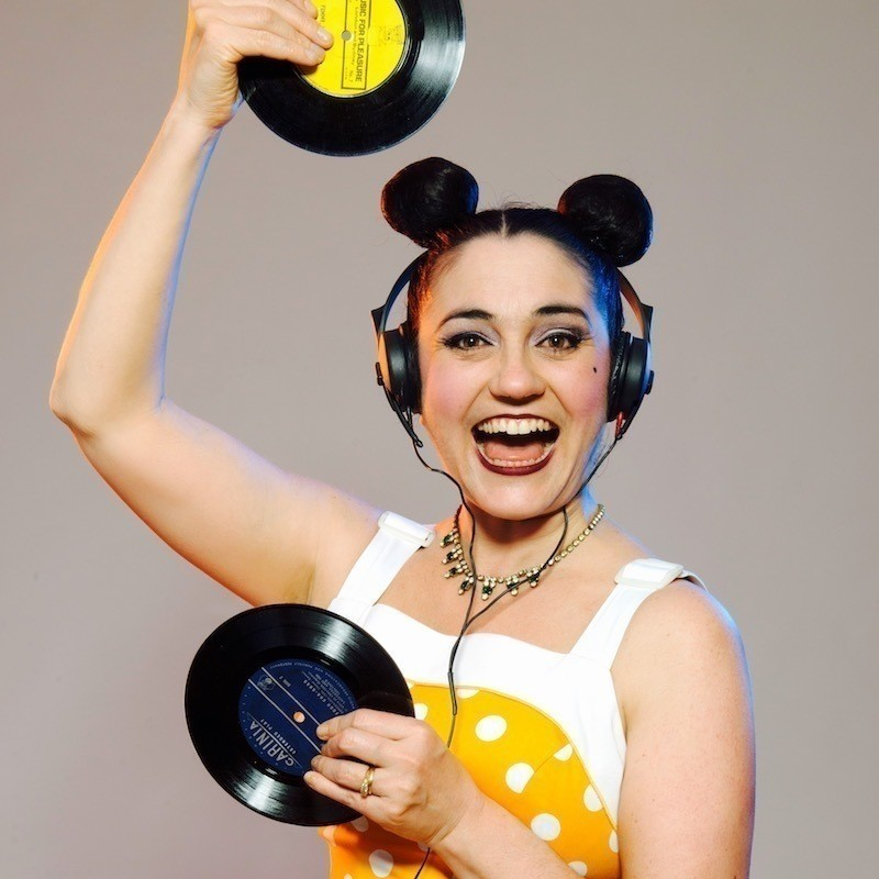 A photo of a woman smiling and wearing headphones and holding two black vinyl discs. Her hair is tied up in two buns on top of her head and she is wearing a yellow and white top.