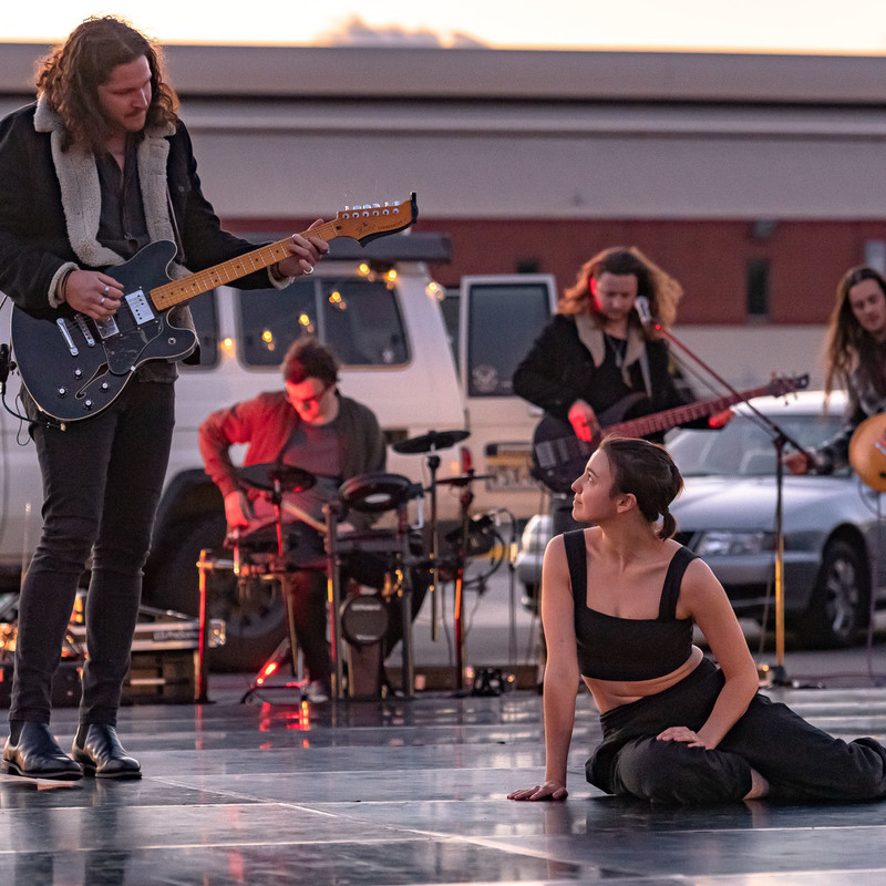 A man playing a guitar locks eyes with a dancer sitting on the floor. A full band is in the background. the yare outside surrounded by cars.