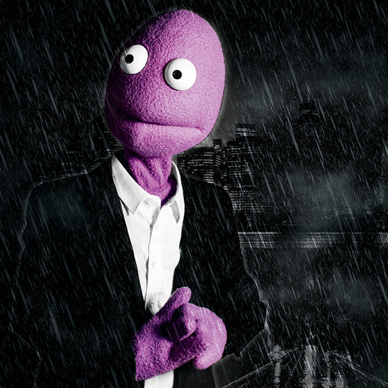 An image of Randy Feltface, a purple puppet with white eyes and a straight mouth. The background of the image features a city skyline at night and rain.