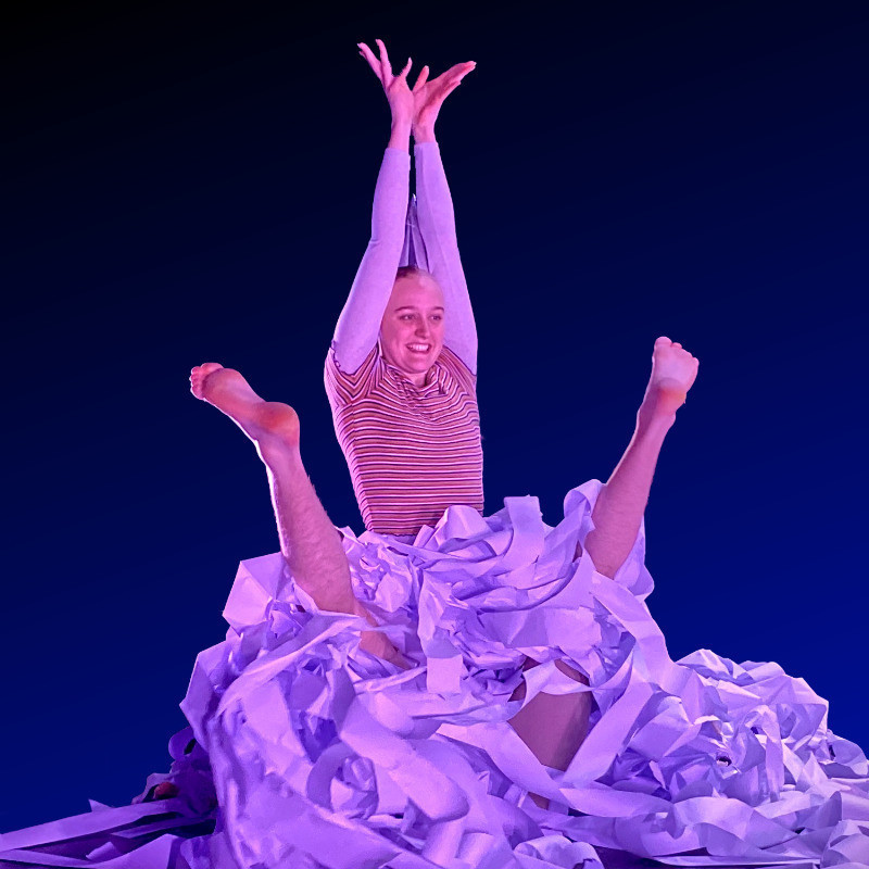 An image of a person standing up with their arms in the air, and two legs poking up in the air. There is a pile of long paper covering the floor and the person with their legs in the air.