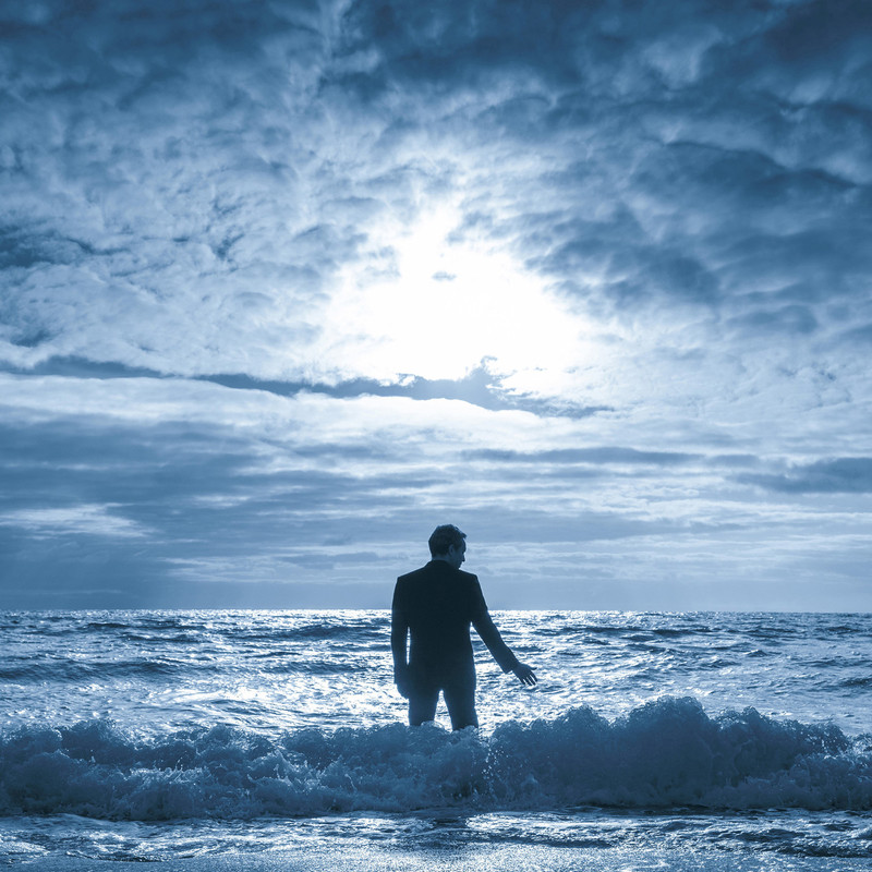 Sea Wall by Simon Stephens - A photo of a person standing in the ocean. The sky is cloudy and overcast.