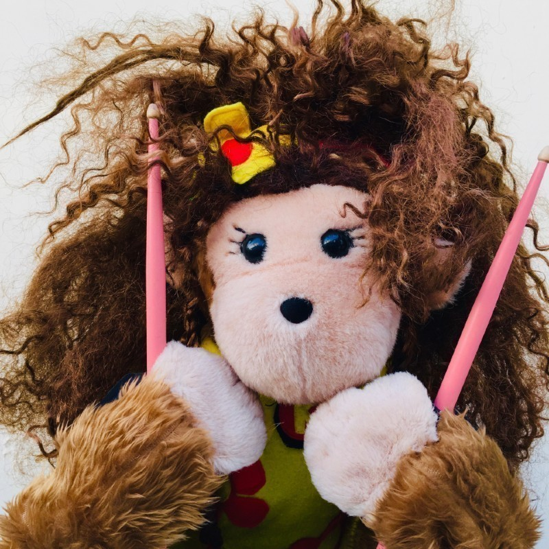 A plush monkey toy with long frizzy brown hair and creamy fur for their face and hands. It is holding pink drumsticks and looking at the camera. It has black eyes with eyelashes and wears a yellow top with red flowers and has a yellow flower in their hair.