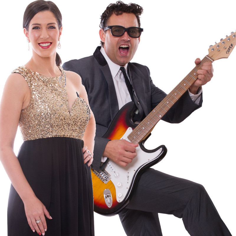 An image of a man and woman. The woman is smiling at the camera. She is wearing a sparkling gold top with a black skirt. The man is wearing a grey suit and is holding a guitar across his body. He has black sunglasses on with a thrilled expression on his face.