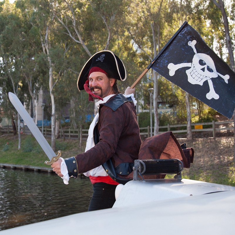 Pirates of Penzance - A photo of a man smiling. He is dressed as a pirate with a brown jacket, white shirt and a black hat with a red bandana. He is holding a plastic sword and black flag with a skull and bones.