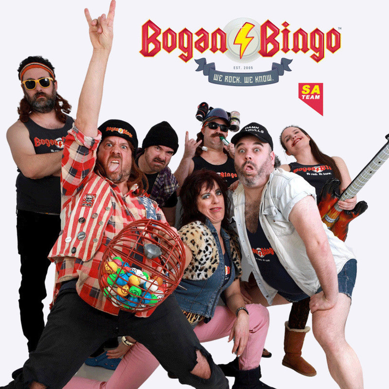 """seven (7) people stand in a group posing in a variety of positions. They are all dressed in 'bogan' attire - singlets, flannelette shirts, fluffy leopard print crop tops, beanies and a hard hat with two beer cans attached. Red sharp angled block letters spell out """"Bogan Bingo"""" with a blue banner below with the text """"we rock. we know."""""""