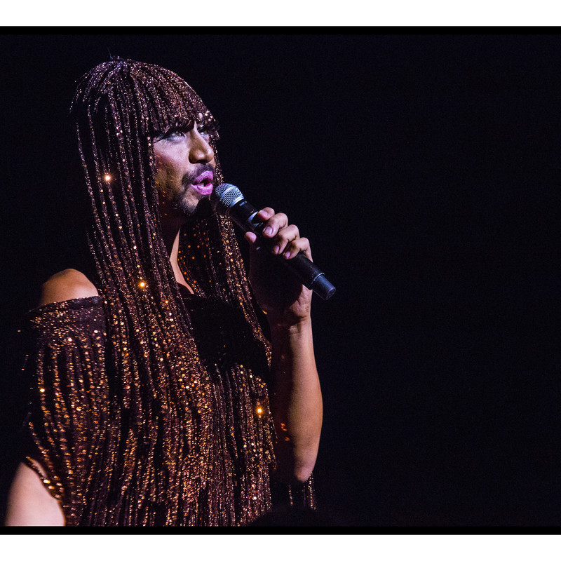 Black List Cabaret - A drag queen with dark skin and a short dark beard stands angled to the left singing into a handheld microphone. They have long fake eyelashes and pink lips. Their wig looks like African braids with sparkling gold strands throughout them, their fringed blouse matches the colour and gold sparkled hair exactly. The background is black.