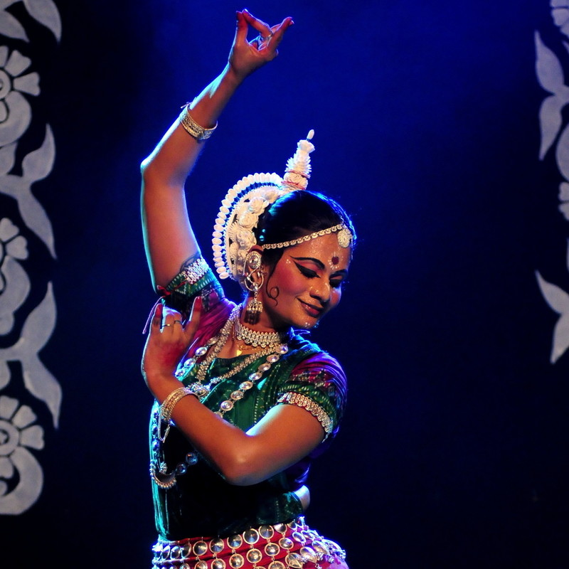 A photograph of an Odissi dancer wearing a classical Indian cultural costume.