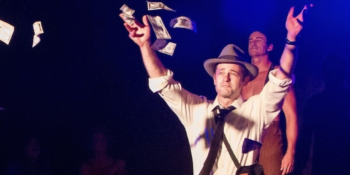A photo of a man with his hands in the air while several notes of money fall around him. He is wearing a faded trilby hat with a white long-sleeve shirt.
