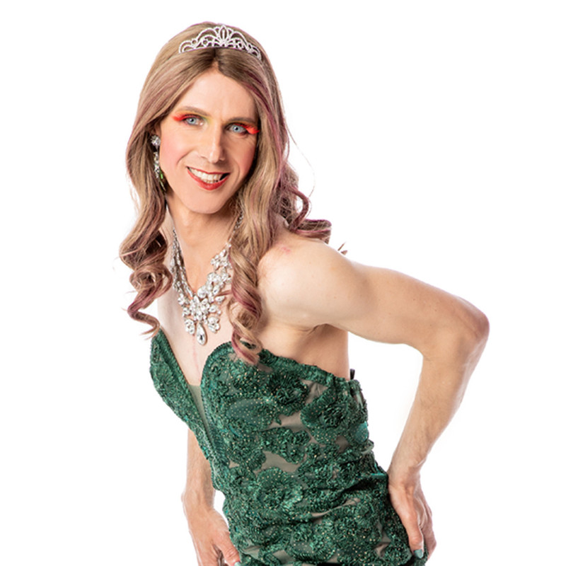 Kiki & The Covid All Stars - A photo of a person wearing a sparkly green strapless dress with a silver tiara and silver necklace. They are wearing bright orange eyeshadow across their eyelids. Their hair is blonde and falls below their shoulder.