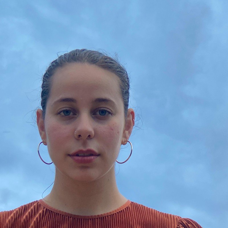 Baby, What Blessings By Siofra Dromgoole - A photo of a woman staring straight ahead. Her hair is tied back and she is wearing large hoop earrings. Her eyes are blue and the top she is wearing is orange. The background is light blue.