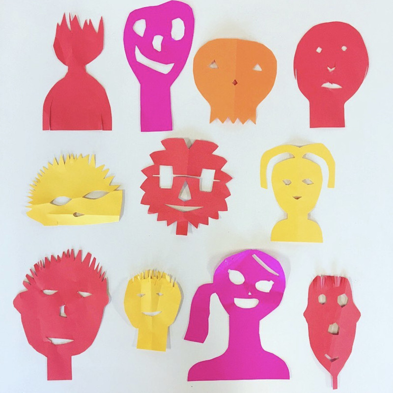 A photo of a collection of twelve abstract faces that have cut out of red, pink, orange and yellow paper on a white background.