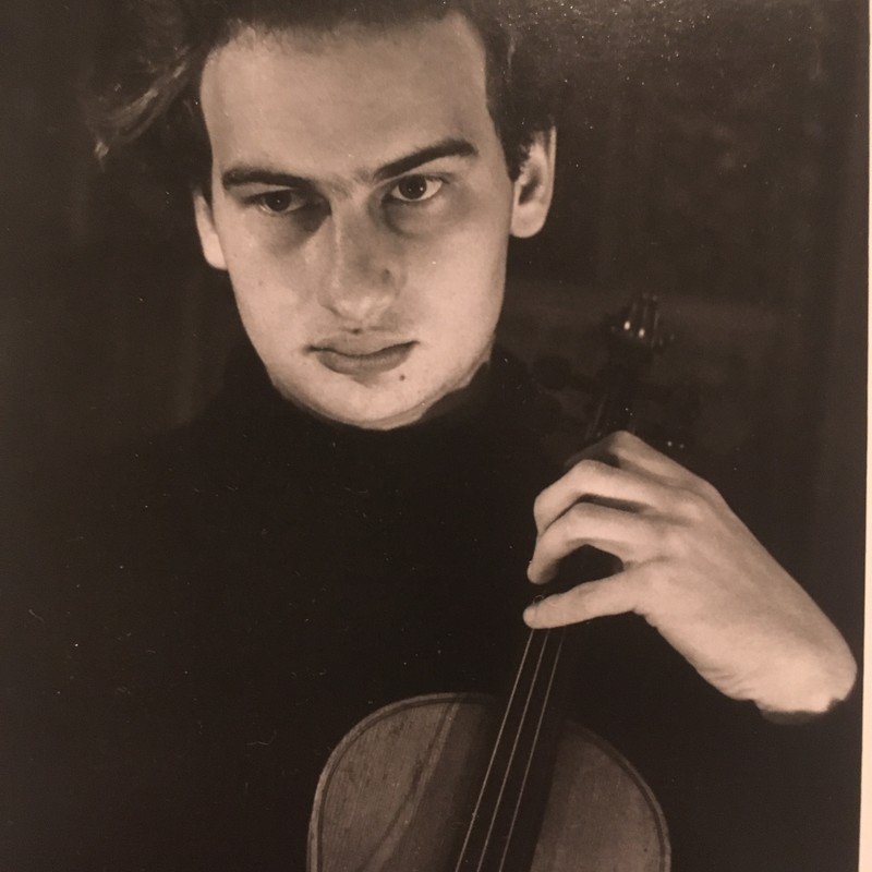 J.S. Bach: The entire works for violin unaccompanied by Jonathon Glonek - A sepia toned photo of a man with dark eyes looking serious holding a violin.