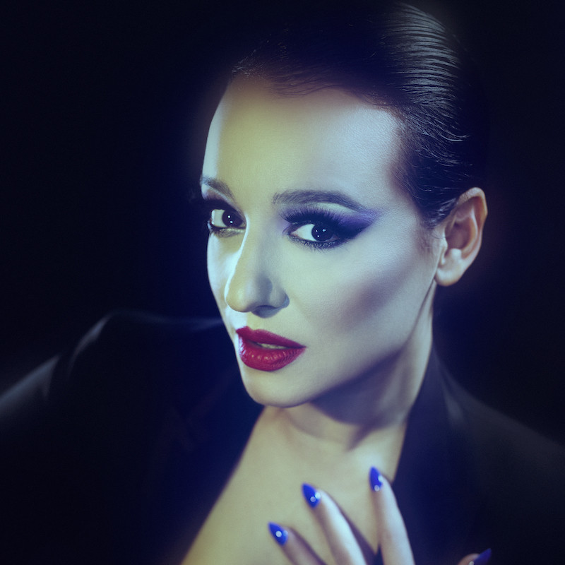 Carla Lippis: New Songs for the New World - A photograph of a woman wearing dramatic purple eyeshadow and red lipstick staring straight into the camera.