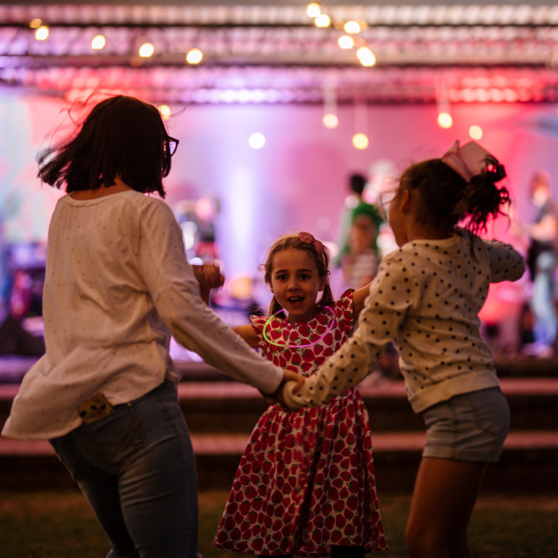 A mother dances with two young children, they are all holding hands. The yare dancing on grass in front of an outdoor stage at twilight.