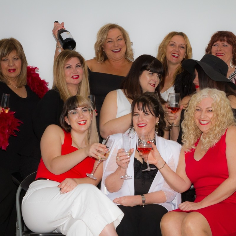 A photo of a group of woman smiling and holding wine glasses. They are all wearing red, white or black clothing items and red lipstick.