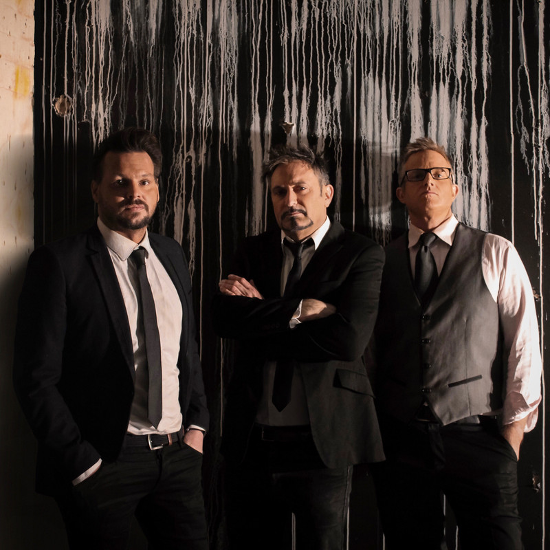 Three men wearing black suit jackets, white shirts and black ties stand looking with blank expressions. The two men on the outer have their hands in their pockets, the man in the centre has his arms crossed. There is white paint dribbling down a black wall in the background.