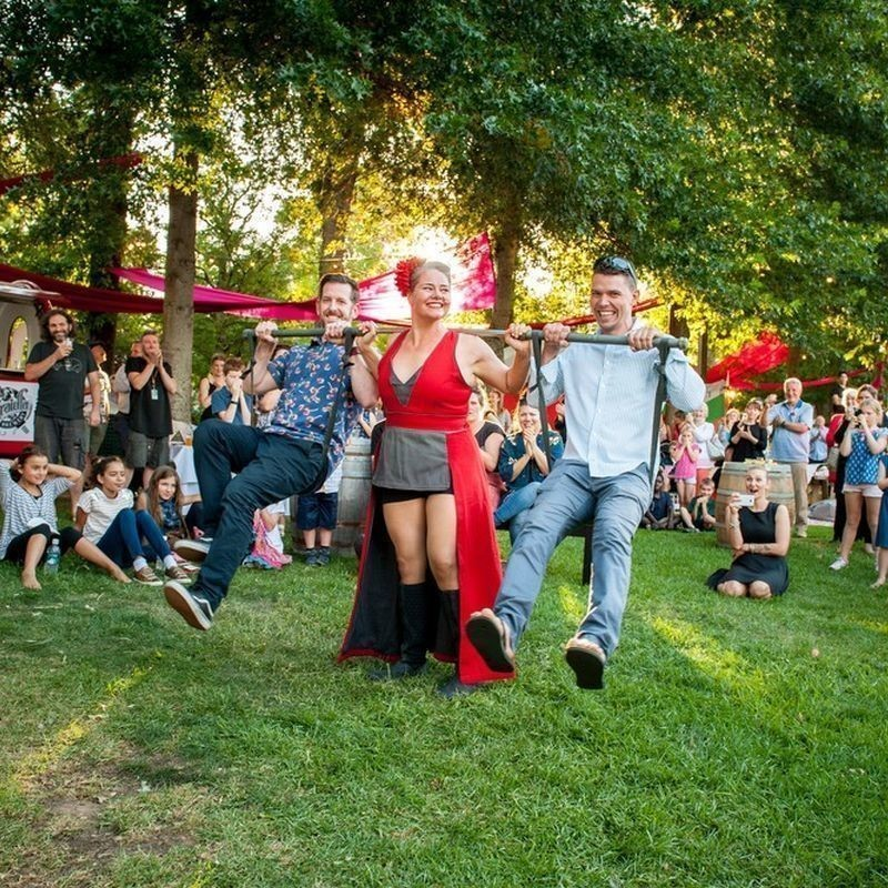 Festival of the Hills: Opening night party - A woman dressed in red and grey costume holds pole over her shoulders while two men sitting suspended on straps either side of her. They are on grass surrounded by trees and a crowd of people.