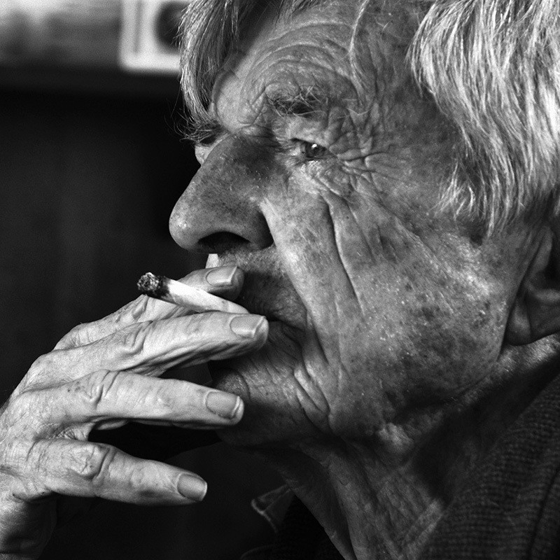 Yer Old Faither - A black and white close up photograph of an older man with white hair smoking a cigarette.