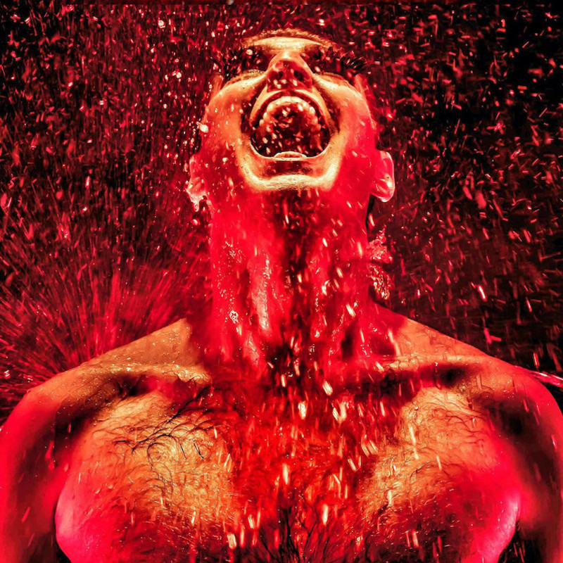 A headshot photo of a shirtless person with their mouth open and their head tilted back. There are water droplets everywhere.
