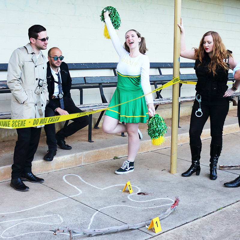 A photo of four people standing around a crime scene. On the ground there is an outline of a body and a wooden stick with evidence marking numbers. In the middle of the image is a woman dressed as a cheerleader and on her right is a woman dressed in all black with handcuffs hanging from her pants. On the left of the image there are two men wearing sunglasses, one is wearing a cream coloured trench coat and the other is wearing a black suit.