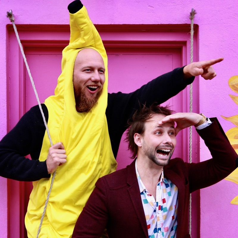 Two men stand in front of a bright pink wall and door. The man on the left is wearing a yellow banana suit pointing to the right. The other man squats under the pointed arm looking where it is pointed with his hand shielding his eyes. He wears a burgundy suit jacket and a white shirt with coloured squares on it. Both men look excited.
