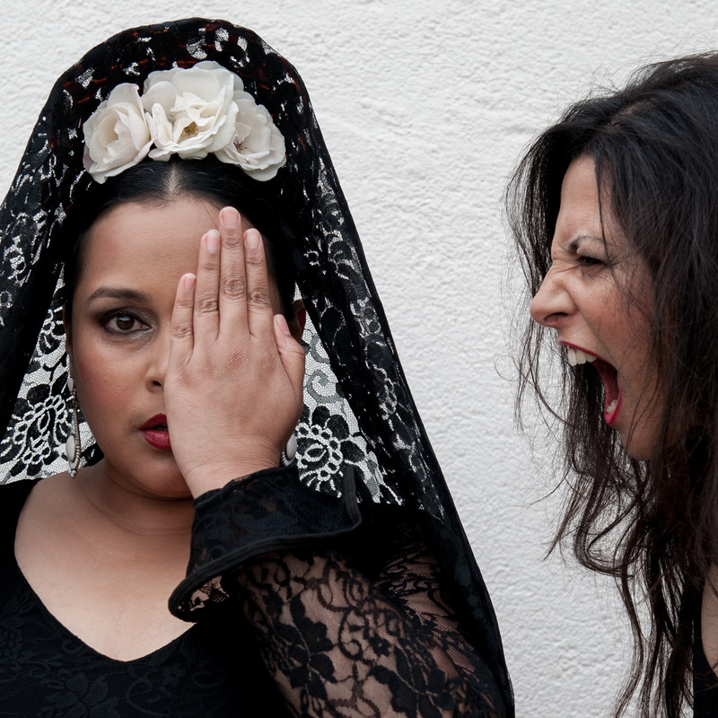 Las Cuatro - A photograph of two women. The woman on the left is facing straight ahead and is wearing a black lacy veil with white roses and has one hand covering half of her face. The woman on the right has a furious facial expression and is turned to face the woman on the left.