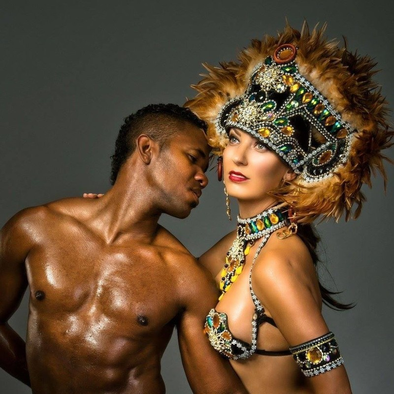 A photo of a woman wearing a black bra embellished with yellow, green and silver gemstones and a matching large headpiece with brown feathers. The man next to her is shirtless and is leaning into her body.