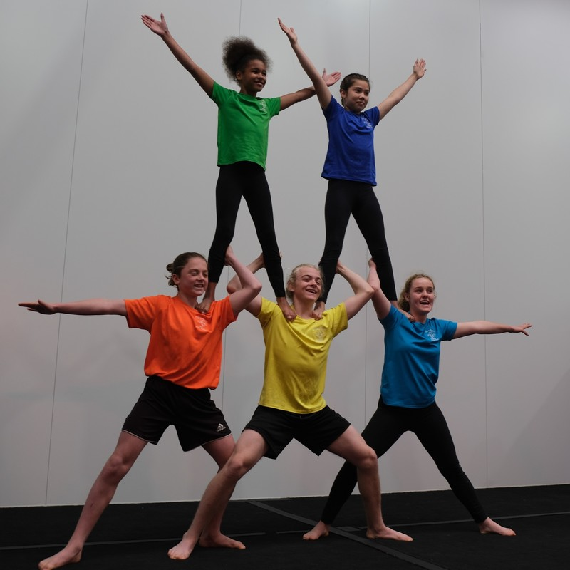 Celebrating Australia - A photo of five kids forming a pyramid. There are three kids wearing an orange, yellow and blue coloured t-shirt standing with their feet wide apart on the ground with the other two kids wearing green and purple t-shirts standing on their shoulders.