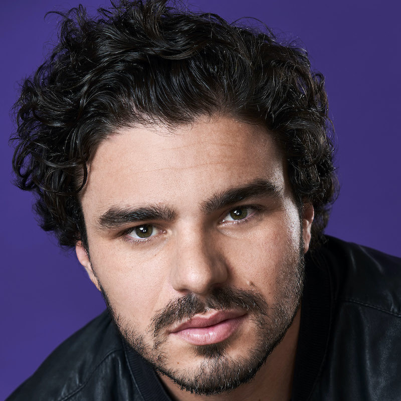 Amos Gill: The Sheeple's Champion - A man with fair skin, thick wavy black hair and stubble stares into the camera. The background is a rich purple.