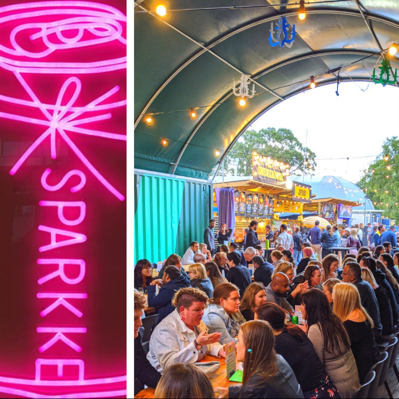 The Fringe Social - An image of multiple long tables of people sitting across from each other. On the left of the image features a neon sign of a can that reads 'Sparkke'.