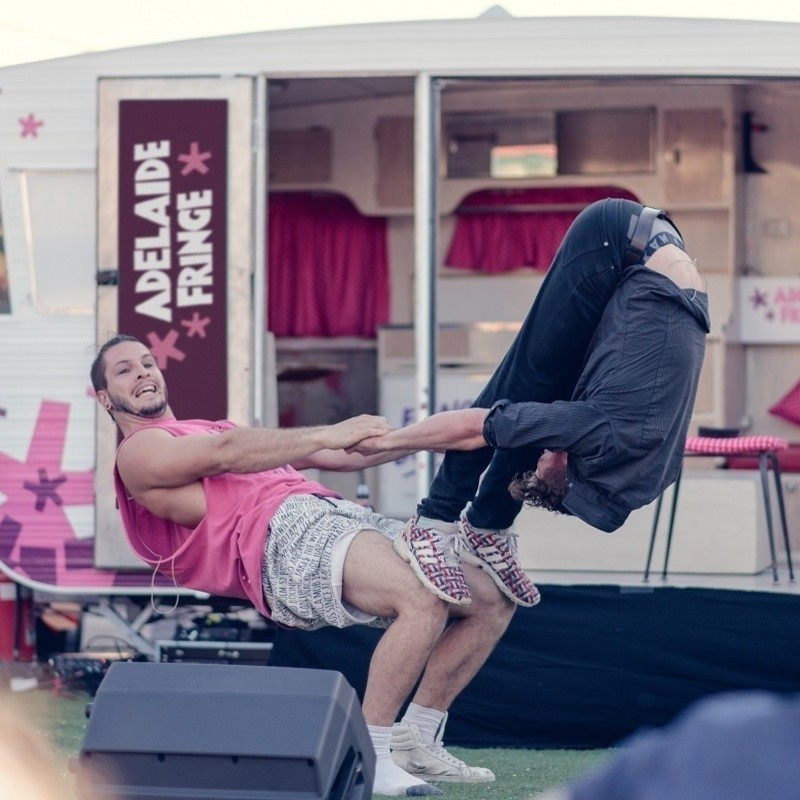 Naracoorte Fringe Street Party - Two acrobats perform a balancing act in front of the Fringe on Tour caravan.