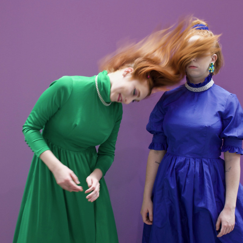 A photo of a person swinging their hair into another person's face. The person swinging their hair is wearing a green dress, and the other person is wearing a blue dress.