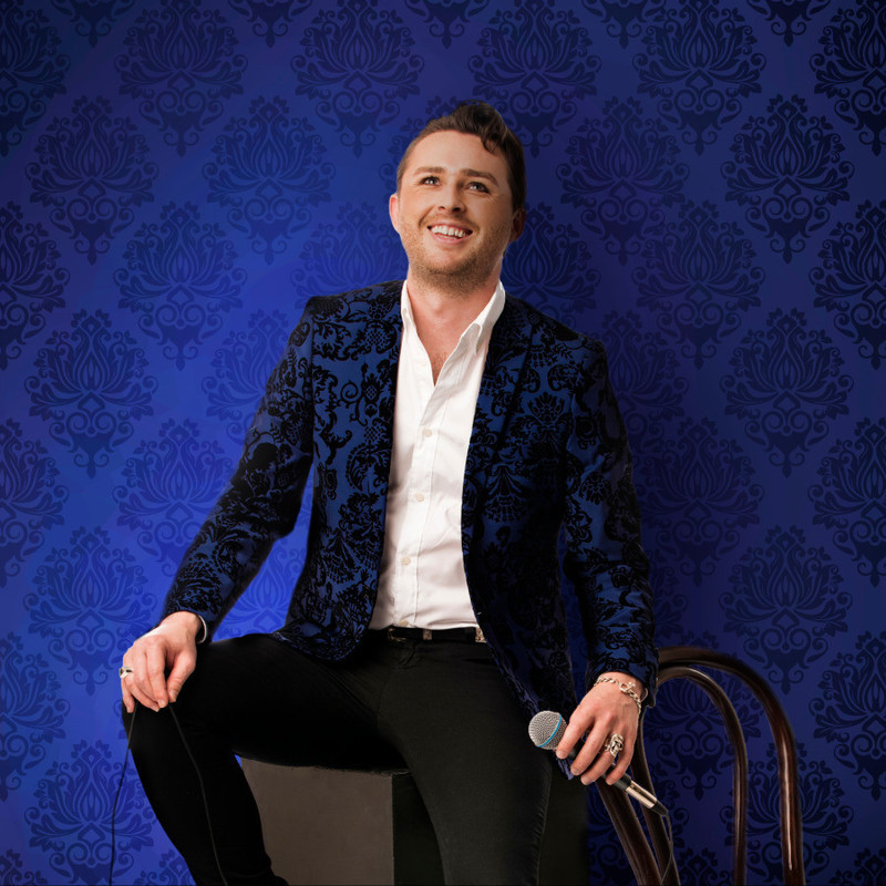 Stewart Reeve: Chameleon - A photo of a person smiling. They are wearing a dark blue jacket with black detailing, white shirt and black pants. The background is dark blue and matches the pattern on the jacket.