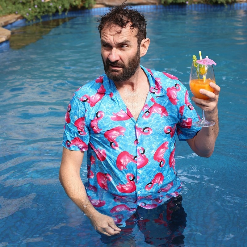 Gordon Southern: Nisolation - A photo of a man standing in a pool with a confused expression. He is wearing a blue shirt with a pink flamingo design and is holding a glass with an orange cocktail in it.